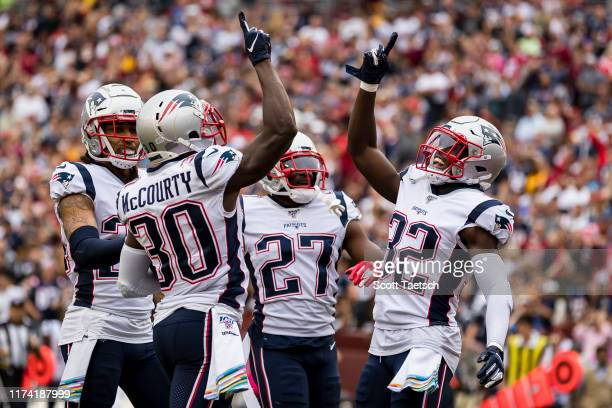 Jason McCourty of the New England Patriots celebrates with teammates after intercepting a pass during the first half against the Washington Redskins...