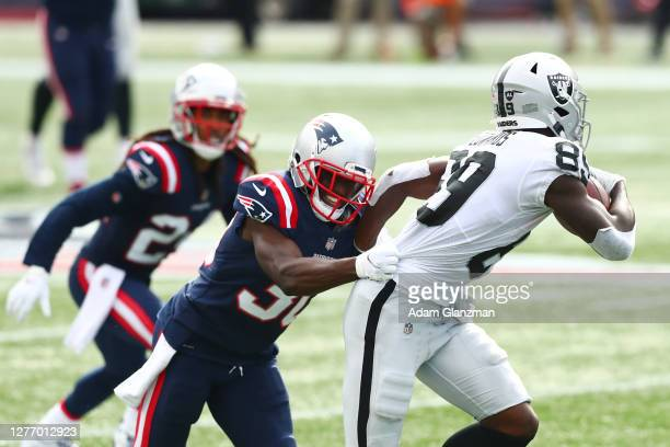 Jason McCourty of the New England Patriots tackles Bryan Edwards of the Las Vegas Raiders during the second half at Gillette Stadium on September 27...