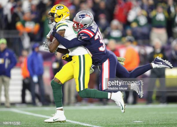 Jason McCourty of the New England Patriots tackles Marquez ValdesScantling of the Green Bay Packers during the second half at Gillette Stadium on...