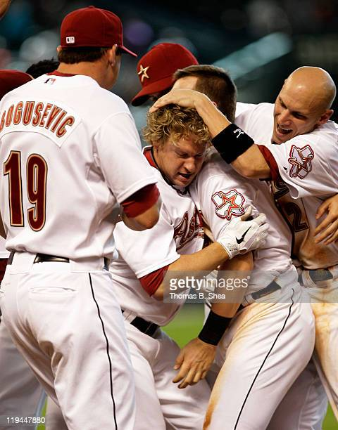 Jason Michael #4 of the Houston Astros is mobbed by teammates after hitting the game winning walk off RBI in the 11th inning against the Washington...