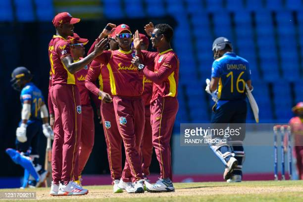 Jason Mohammed , Akeal Hosein and Alzarri Joseph of West Indies celebrate the dismissal of Dimuth Karunaratne of Sri Lanka during the 3rd and final...