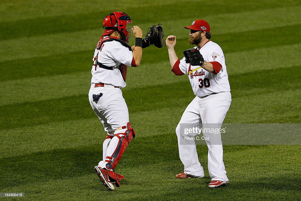 Jason Motte #30 and catcher Yadier Molina #4 of the St. Louis Cardinals celebrate the Cardinals 3-1 victory against the San Francisco Giants in Game Three of the National League Championship Series at Busch Stadium on October 17, 2012 in St Louis, Missouri.