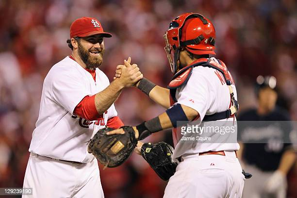 Jason Motte and Yadier Molina of the St Louis Cardinals celebrate after they won 71 against the Milwaukee Brewers during Game Five of the National...