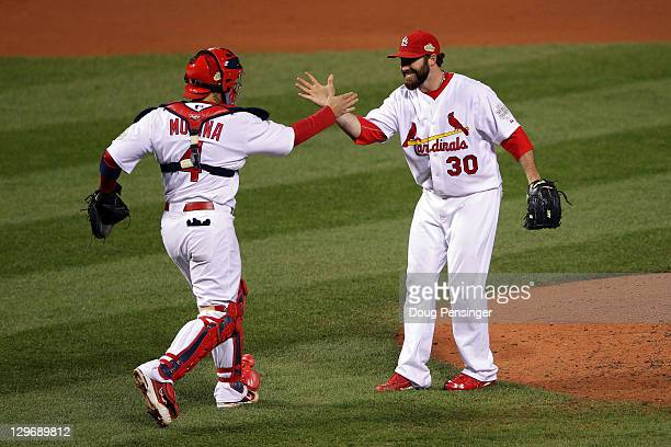 Jason Motte and Yadier Molina of the St Louis Cardinals celebrate after defeating the Texas Rangers 32 during Game One of the MLB World Series at...