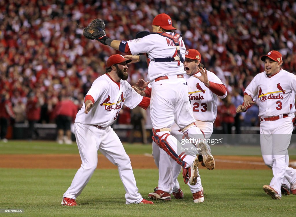 Jason Motte #30 and Yadier Molina #4 of the St. Louis Cardinals celebrate after defeating the Texas Rangers 6-2 to win Game Seven of the MLB World Series at Busch Stadium on October 28, 2011 in St Louis, Missouri.