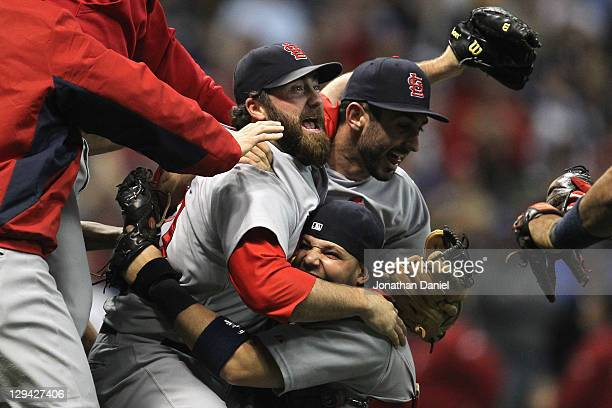 Jason Motte Daniel Descalso and Yadier Molina of the St Louis Cardinals celebrate after they won 126 against the Milwaukee Brewers during Game Six of...