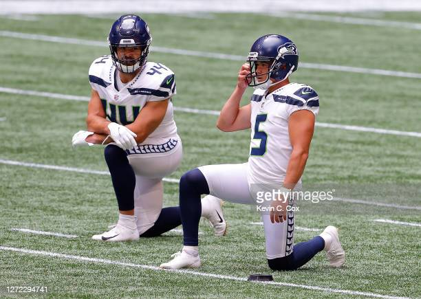 Jason Myers and Nick Bellore of the Seattle Seahawks kneel after the opening kickoff against the Atlanta Falcons at Mercedes-Benz Stadium on...