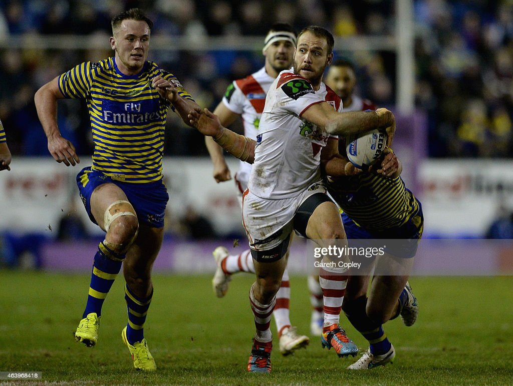 Jason Nightingale of St George Illawarra Dragons gets past Ben Currie and Ben Westwood of Warrington Wolves during the World Club Series match between Warrington Wolves and St George Illawarra Dragons at The Halliwell Jones Stadium on February 20, 2015 in Warrington, England.
