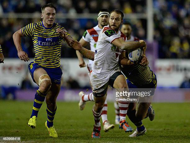 Jason Nightingale of St George Illawarra Dragons gets past Ben Currie and Ben Westwood of Warrington Wolves during the World Club Series match...