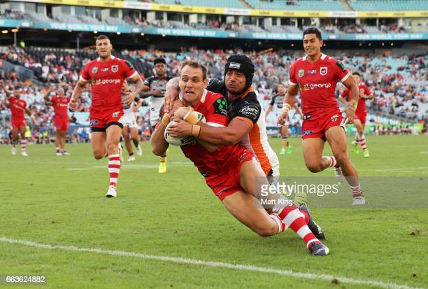 Jason Nightingale of the Dragons beats David Nofoaluma of the Tigers to score a try during the round five NRL match between the Wests Tigers and the...