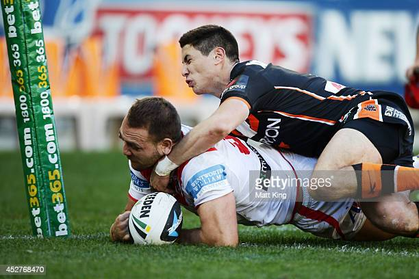 Jason Nightingale of the Dragons beats Mitchell Moses of the Tigers to score a try during the round 20 NRL match between the Wests Tigers and the St...