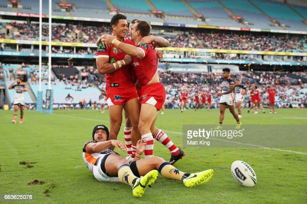 Jason Nightingale of the Dragons celebrates with team mates after scoring a try as David Nofoaluma of the Tigers looks on during the round five NRL...