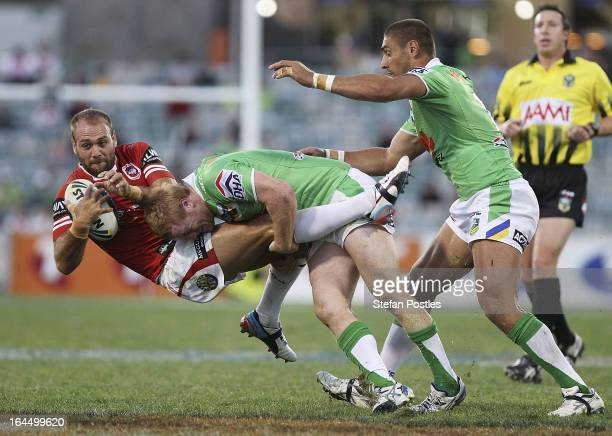 Jason Nightingale of the Dragons is tackled by Joel Edwards of the Raiders during the round three NRL match between the Canberra Raiders and the St...