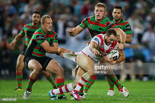 Jason Nightingale of the Dragons is tackled by the pants by Jason Clark of the Rabbitohs during the round 12 NRL match between the South Sydney...