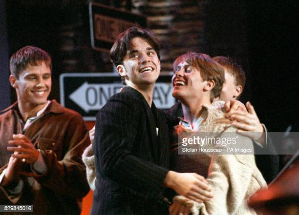 Jason Orange Robbie Williams and Mark Owen of the teen band Take That celebrating on stage after taking three awards at the Smash Hits Poll Winners...