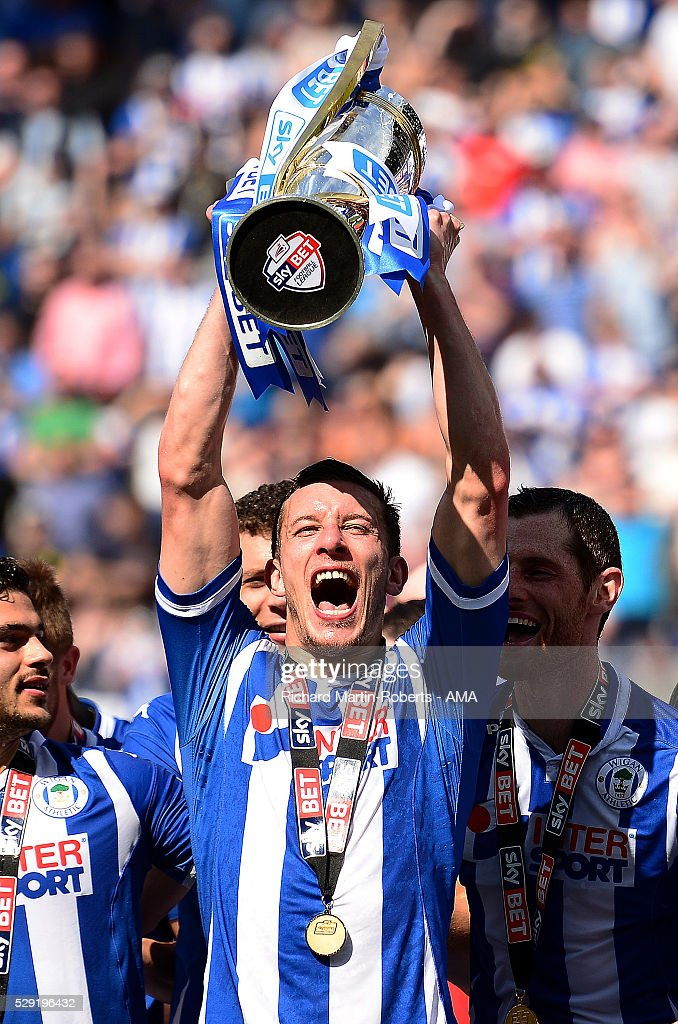 Jason Pearce of Wigan Athletic lifts the Sky Bet League One trophy as Wigan celebrate winning the 2015/16 Sky Bet League One Championship at the end of the Sky Bet League One match between Wigan Athletic and Barnsley at DW Stadium on May 8, 2016 in Wigan, England.