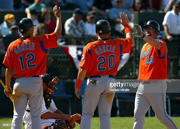 Jason Phillips of the New York Mets is congratulated by teammates Danny Garcia and Karim Garcia after hitting a three run home run in the top of the...