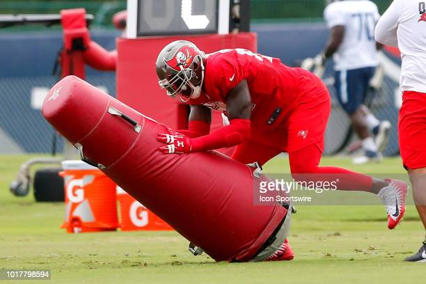 Jason PierrePaul of the Bucs knocks down the blocking dummy during the joint training camp work out between the Tampa Bay Buccaneers and the...