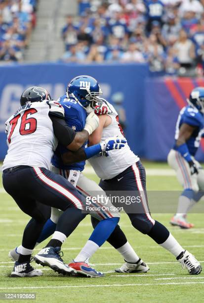 Jason Pierre-Paul of the New York Giants fights off the block of Duane Brown and Ben Jones of the Houston Texans during an NFL football game...