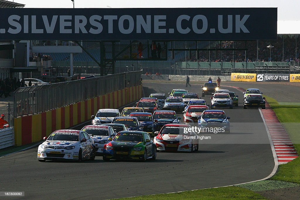 Jason Plato drives the #99 MG KX Momentum Racing MG6 leads Colin Turkington driving the #29 eBay Motors BMW 125i Sport and the field at the start of the Dunlop MSA British Touring Car Championship race at the Silverstone Circuit on September 29, 2013 in Towcester, United Kingdom.