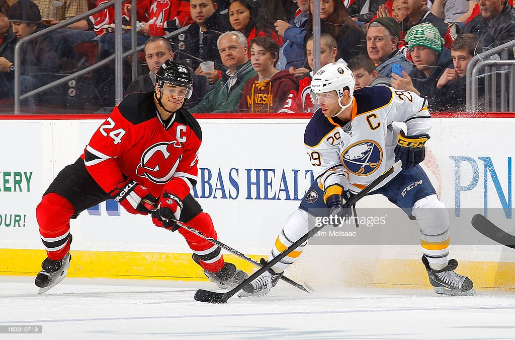 Jason Pominville #29 of the Buffalo Sabres plays the puck against Bryce Salvador #24 of the New Jersey Devils at the Prudential Center on March 7, 2013 in Newark, New Jersey.