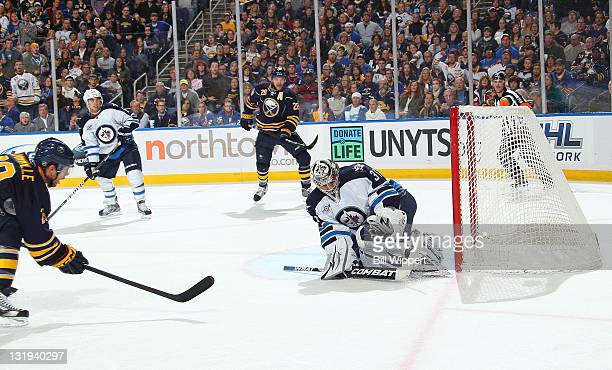 Jason Pominville of the Buffalo Sabres scores a first period shorthand goal against Ondrej Pavelec of the Winnipeg Jets on a pass from teammate Paul...