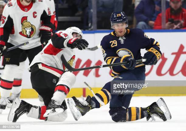 Jason Pominville of the Buffalo Sabres tries to tip a shot as Alexandre Burrows of the Ottawa Senators defends during the first period at the KeyBank...