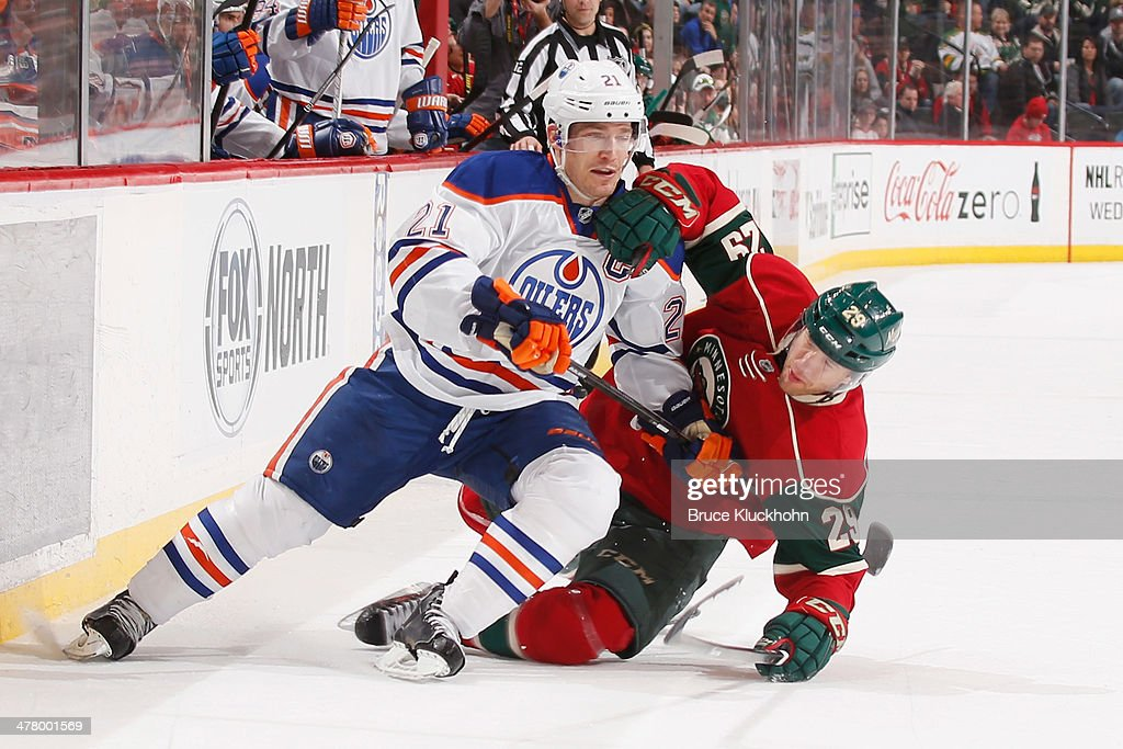 Jason Pominville #29 of the Minnesota Wild falls while defending Andrew Ference #21 of the Edmonton Oilers during the game on March 11, 2014 at the Xcel Energy Center in St. Paul, Minnesota.