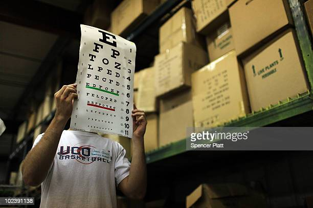 Jason Quint a medical student holds up an eye exam for a patient in a garage at a flower nursery serving as a healthcare clinic for migrant farm...