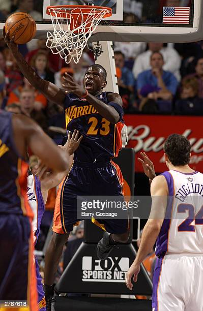Jason Richardson of the Golden State Warriors dunks against the Phoenix Suns at America West Arena on November 28 2003 in Phoenix Arizona NOTE TO...