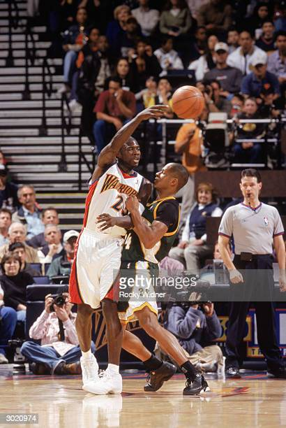Jason Richardson of the Golden State Warriors passes over Ray Allen of the Seattle Sonics during the game on February 21 2004 at the Arena in Oakland...