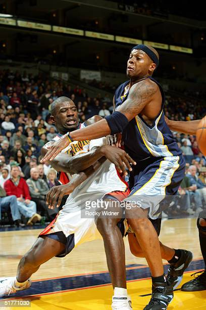 Jason Richardson of the Golden State Warriors passes the ball around Stromile Swift of the Memphis Grizzlies at the Arena in Oakland on November 20...