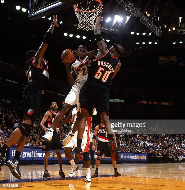 Jason Richardson of the Golden State Warriors takes the ball to the basket against Zach Randolph and Theo Ratliff of the Portland Trail Blazers...