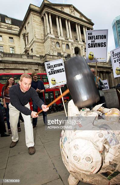 Jason Riddle cofounder of 'Save Our Savers' uses a giant hammer to smash a papier mache piggy bank outside the Bank of England in London on October 6...