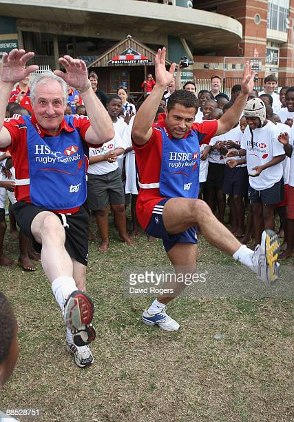 Jason Robinson of British and Irish Lions and former British and Irish Lions player Gareth Edwards dance with children as they sing Shosholoza during...