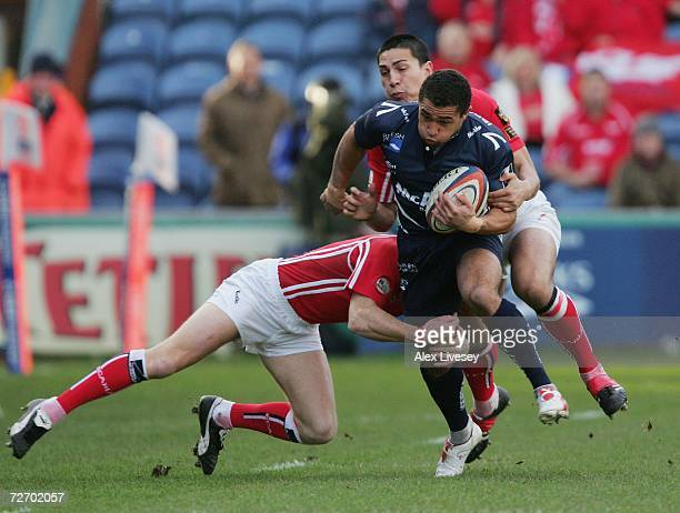 Jason Robinson of Sale Sharks is tackled by Garan Evans and Regan King of Llanelli Scarlets during the EDF Energy Cup match between Sale Sharks and...