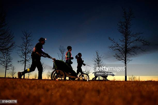 Jason Romero uses a headlamp and a stroller with headlights to add contrast to to the roadway on a pre-dawn run with his coach Carly Gerhart, friend...