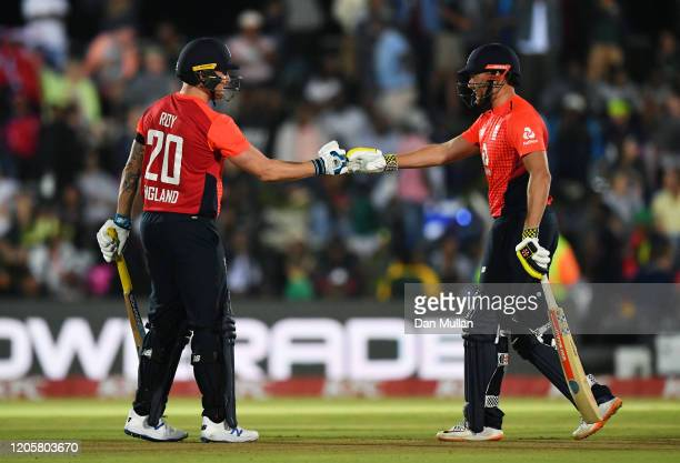 Jason Roy and Jonny Bairstow of England punch gloves during the First T20 International match between South Africa and England at Buffalo Park on...