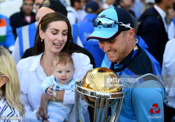 Jason Roy of England holds the trophy as his family look on after the Final of the ICC Cricket World Cup 2019 between New Zealand and England at...