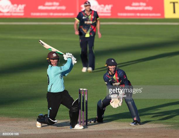 Jason Roy of Surrey hits a boundary as Kent Spitfires wicket keeper Sam Billings looks on during the NatWest T20 Blast South Group match between Kent...
