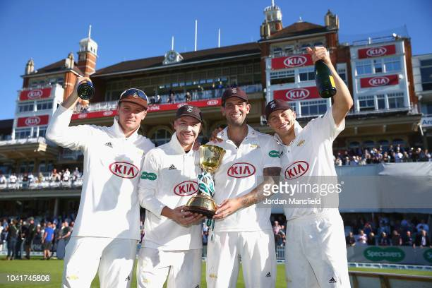 Jason Roy, Rory Burns, Jade Dernbach and Tom Curran of Surrey celebrates with the Specsavers County Championship Division One Cup during Day Four of...