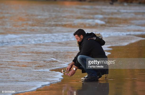 Jason Ruszczyk the brother of Justine Damond is seen placing a flower into the water during a vigil for his sister at Freshwater Beach on July 19...