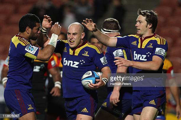 Jason Rutledge of the Highlanders celebrates with Alando Soakai and Ben Smith after scoring during the round 12 Super Rugby match between the Chiefs...