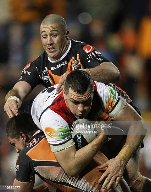 Jason Ryles of the Roosters is tackled during the round 20 NRL match between the Wests Tigers and the Sydney Roosters at Leichhardt Oval on July 23...