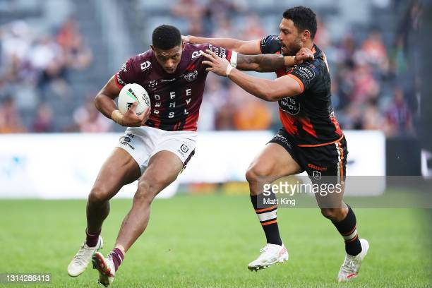 Jason Saab of the Sea Eagles is tackled by David Nofoaluma of the Tigers during the round seven NRL match between the Wests Tigers and the Manly Sea...