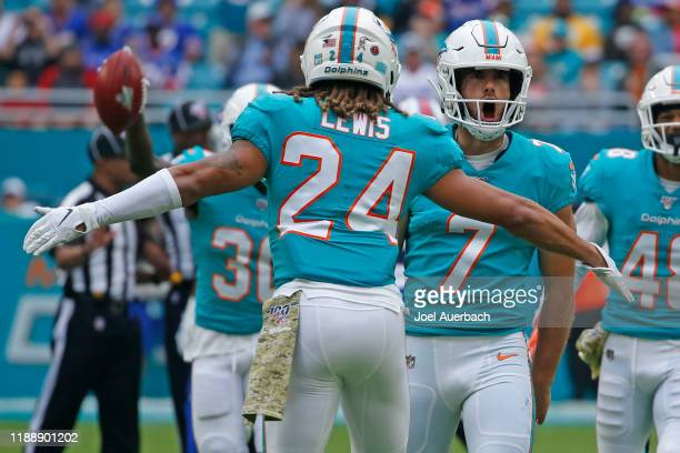 Jason Sanders celebrates recovering his onside kick with Ryan Lewis of the Miami Dolphins against the Buffalo Bills during an NFL game on November...