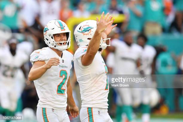 Jason Sanders of the Miami Dolphins celebrates with Matt Haack after kicking the game winning field goal against the Chicago Bears in overtime at...