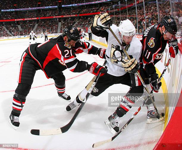 Jason Smith and Daniel Alfredsson of the Ottawa Senators defend against Matt Cooke of the Pittsburgh Penguins along the boards at Scotiabank Place on...