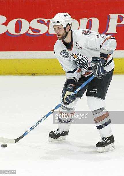 Jason Smith of the Edmonton Oilers looks to pass the puck against the Calgary Flames on March 9 2004 at The Pengrowth Saddledome in Calgary Alberta...