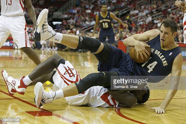 Jason Smith of the New Orleans Pelicans falls on Terrence Jones of the Houston Rockets in a preseason NBA game on October 5 2013 at Toyota Center in...